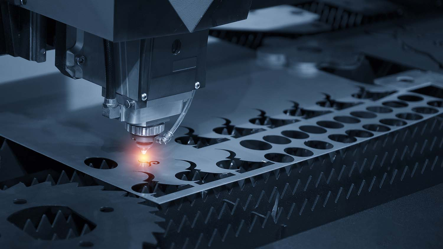 The CNC laser cut machine while cutting the sheet metal with the